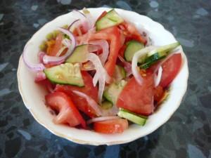 Заготавливаем салат из огурцов, помидоров и лука.